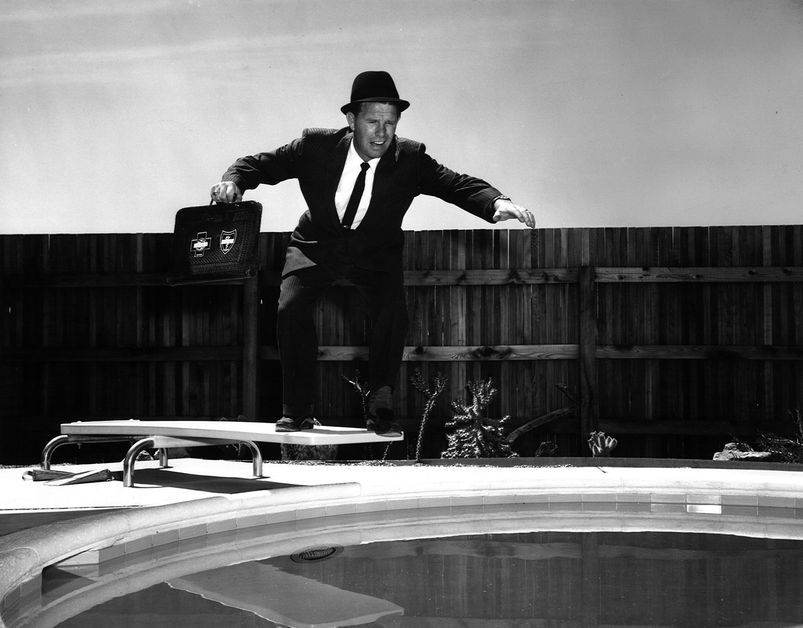 Businessman jumping in a pool