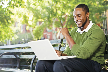 Man sitting on bench viewing his laptop