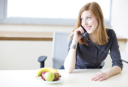 Female on phone with fruit in front of her