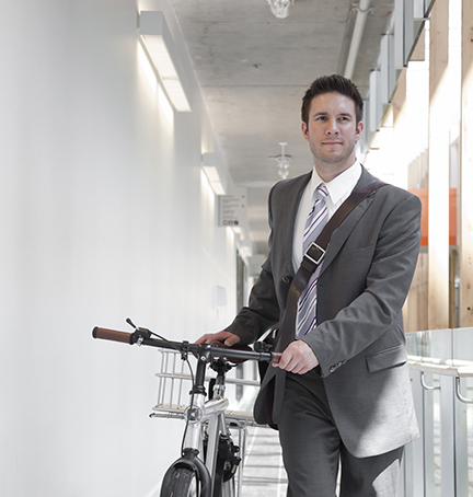 Professional male with a bike in hallway